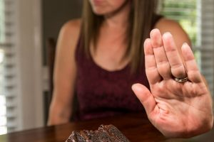 Woman Resisting temtation by not eating Chocolate Cake